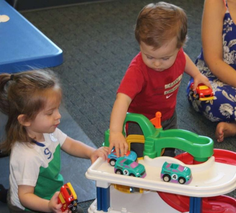 Two toddlers playing with child car toy