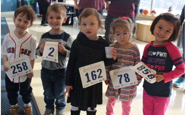 Children holding up their runner bibs