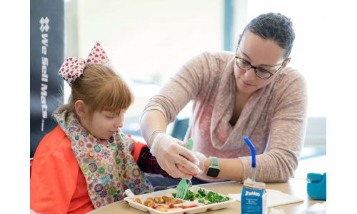 Teacher assisting in feeding a student