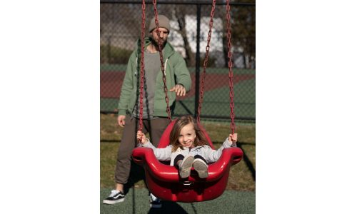 Child happy on a swing being pushed by parental figure
